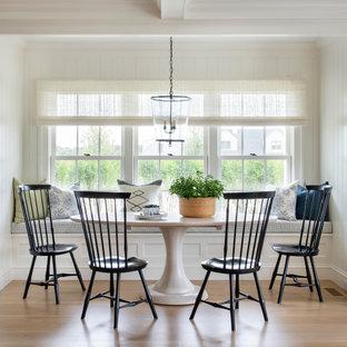 Ispirazione per una sala da pranzo costiera con pareti bianche, pavimento in legno massello medio, pavimento marrone e pareti in perlinato