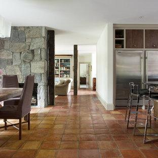 Modelo de comedor rural con marco de chimenea de piedra y suelo de baldosas de terracota