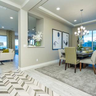 Esempio di una grande sala da pranzo aperta verso il soggiorno minimal con pareti beige, pavimento in gres porcellanato e pavimento grigio