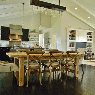 Foto di una sala da pranzo aperta verso il soggiorno country con pareti bianche e parquet scuro
