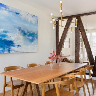 Idée de décoration pour une salle à manger design avec un mur blanc, un sol en bois brun et un sol marron.