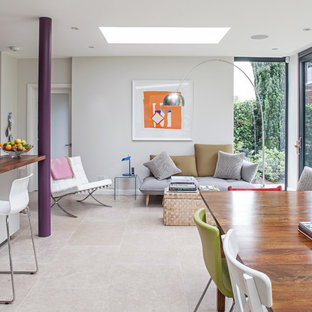 Imagen de comedor contemporáneo, abierto, con paredes blancas y suelo de travertino