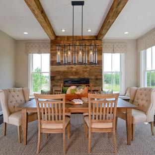 Modelo de comedor rural, grande, cerrado, con paredes beige, suelo de madera en tonos medios, chimenea tradicional y marco de chimenea de madera