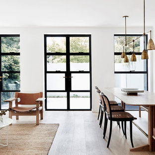 This is an example of a scandinavian open plan dining in Sydney with white walls, medium hardwood floors and brown floor.