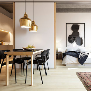This is an example of a medium sized contemporary dining room in London with white walls and light hardwood flooring.