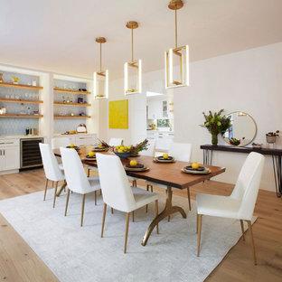 Foto di una grande sala da pranzo aperta verso la cucina classica con pareti bianche, parquet chiaro, camino ad angolo, cornice del camino in intonaco e pavimento bianco