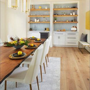 Immagine di una grande sala da pranzo aperta verso la cucina chic con pareti bianche, parquet chiaro, camino ad angolo, cornice del camino in intonaco e pavimento bianco