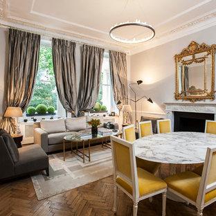Ispirazione per una sala da pranzo aperta verso il soggiorno vittoriana con pareti grigie, camino classico e pavimento in legno massello medio