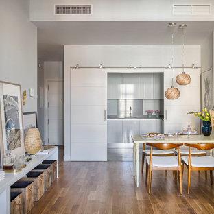 Ejemplo de comedor de cocina ecléctico, de tamaño medio, sin chimenea, con paredes blancas y suelo de madera en tonos medios