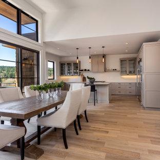 Esempio di una sala da pranzo aperta verso il soggiorno chic di medie dimensioni con pareti bianche, pavimento marrone e pavimento in laminato
