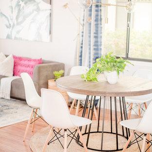 Idee per una sala da pranzo boho chic di medie dimensioni con pareti grigie, pavimento in laminato, camino classico, cornice del camino in legno e pavimento marrone