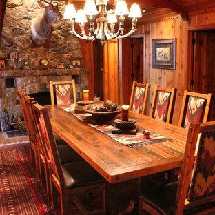 Ispirazione per una grande sala da pranzo aperta verso la cucina stile rurale con pareti multicolore, parquet chiaro, camino bifacciale e cornice del camino in pietra