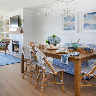 Ejemplo de comedor costero, de tamaño medio, abierto, con paredes blancas, suelo de madera en tonos medios, chimenea tradicional y marco de chimenea de baldosas y/o azulejos