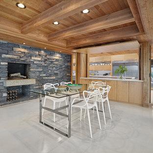 Foto de comedor rural, grande, abierto, con chimenea tradicional, marco de chimenea de piedra, suelo blanco, paredes marrones y suelo de cemento