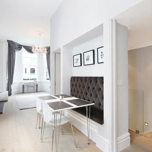 Diseño de comedor contemporáneo, pequeño, abierto, con paredes grises, suelo de madera clara, chimenea tradicional y marco de chimenea de madera