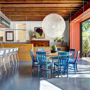 Ejemplo de comedor de cocina industrial con paredes blancas y suelo de cemento
