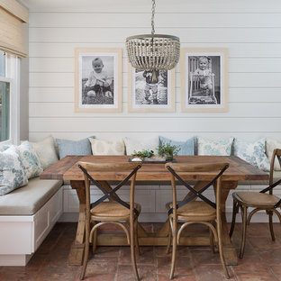 Example of a beach style terra-cotta floor and brown floor dining room design in Other with white walls