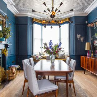 Mittelgroßes Stilmix Esszimmer mit blauer Wandfarbe, hellem Holzboden, Kaminofen, gefliester Kaminumrandung und beigem Boden in Hertfordshire