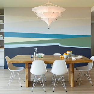 Immagine di una sala da pranzo minimalista con pareti multicolore e parquet chiaro