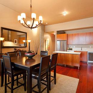 Idee per una piccola sala da pranzo aperta verso la cucina etnica con pareti gialle, parquet scuro e pavimento rosso