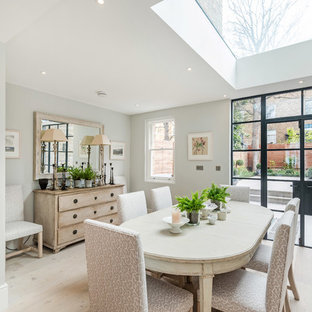 Classic dining room in London with white walls, light hardwood flooring, no fireplace and beige floors.