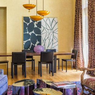 Modelo de comedor ecléctico, grande, abierto, con paredes amarillas, suelo de madera clara, chimenea tradicional, marco de chimenea de hormigón y suelo amarillo