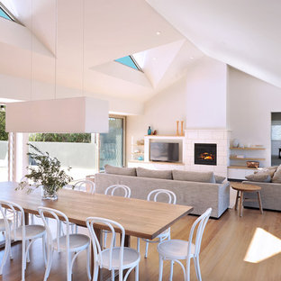 Design ideas for a large contemporary open plan dining in Other with white walls, light hardwood floors, a stone fireplace surround, a standard fireplace and brown floor.