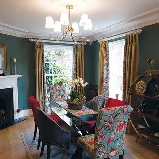 Imagen de comedor clásico, de tamaño medio, con paredes verdes, suelo de madera en tonos medios y chimenea de esquina