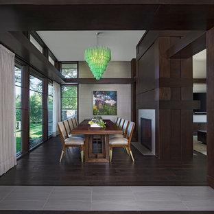 Foto di una grande sala da pranzo aperta verso il soggiorno contemporanea con pareti con effetto metallico, parquet scuro, camino bifacciale, cornice del camino piastrellata e pavimento marrone