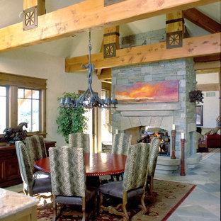 Idee per una grande sala da pranzo rustica chiusa con pareti beige, camino bifacciale, cornice del camino in pietra e pavimento multicolore