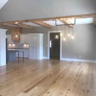 Неиссякаемый источник вдохновения для домашнего уюта: большая гостиная-столовая в стиле кантри с серыми стенами, светлым паркетным полом, бежевым полом и балками на потолке без камина