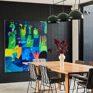 Esempio di una sala da pranzo aperta verso la cucina contemporanea di medie dimensioni con pareti nere, pavimento in cemento, pavimento grigio e pareti in perlinato
