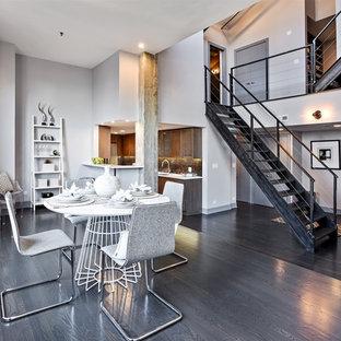 Esempio di una sala da pranzo aperta verso il soggiorno industriale con pareti grigie