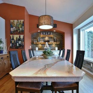 Foto di una sala da pranzo tradizionale chiusa e di medie dimensioni con pareti arancioni, parquet chiaro e nessun camino