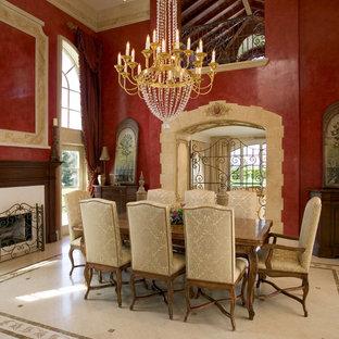 Cette image montre une très grand salle à manger ouverte sur la cuisine traditionnelle avec un mur rouge, un sol en marbre et une cheminée standard.