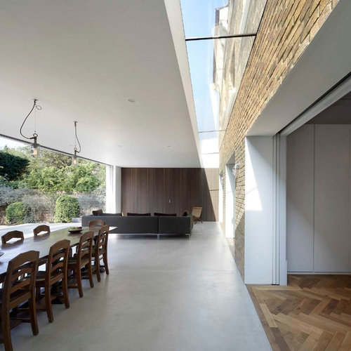 example of a minimalist concrete floor dining room design in london