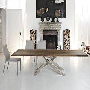 Réalisation d'une grande salle à manger ouverte sur le salon minimaliste avec un mur blanc, béton au sol, une cheminée standard, un manteau de cheminée en pierre et un sol blanc.