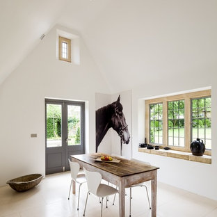 This is an example of a farmhouse enclosed dining room in Gloucestershire with white walls, limestone flooring and beige floors.