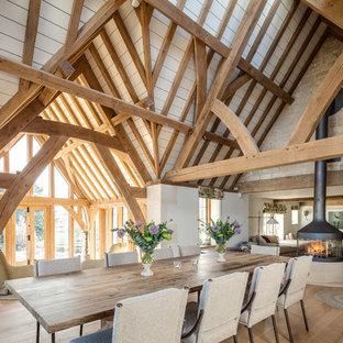 Ejemplo de comedor rural, grande, abierto, con paredes blancas, suelo de madera clara, estufa de leña y suelo beige