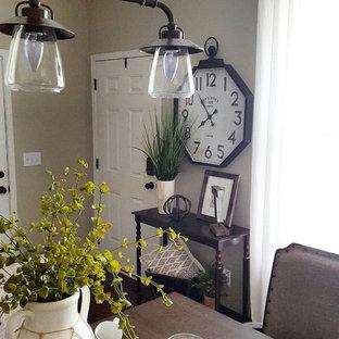 Idee per una sala da pranzo aperta verso la cucina country di medie dimensioni con pareti beige, parquet scuro, camino sospeso, cornice del camino in legno e pavimento marrone