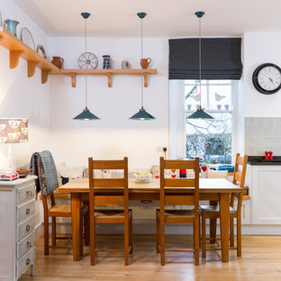 Rural kitchen/dining room in Devon with white walls, light hardwood flooring and beige floors.