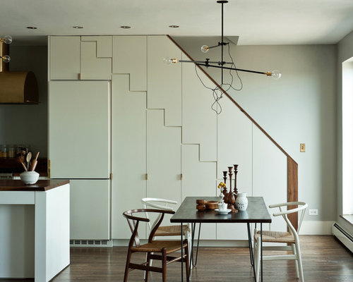 minimalist kitchendining combo photo in new york with gray walls and dark hardwood floors - Under Stairs Kitchen Storage