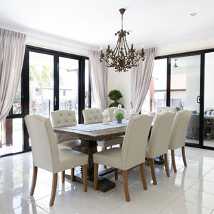 This is an example of a transitional dining room in Brisbane with white walls, no fireplace and white floor.