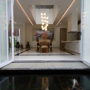 Imagen de comedor de cocina asiático, grande, con paredes blancas y suelo de mármol