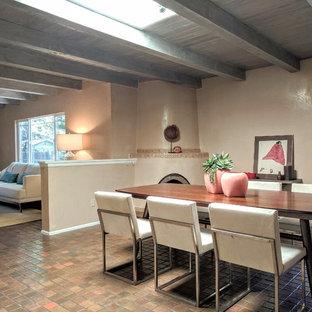 Ejemplo de comedor de cocina de estilo americano, de tamaño medio, con paredes beige, suelo de baldosas de terracota, chimenea de esquina, marco de chimenea de yeso y suelo marrón