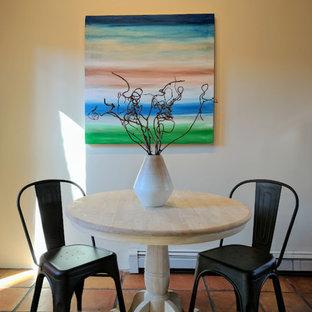 Foto di una piccola sala da pranzo aperta verso la cucina stile americano con pareti gialle, pavimento in terracotta e nessun camino