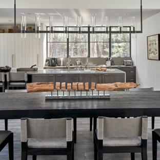 Inspiration pour une salle à manger ouverte sur le salon rustique de taille moyenne avec un mur blanc, un sol en bois clair, un sol gris et du lambris de bois.