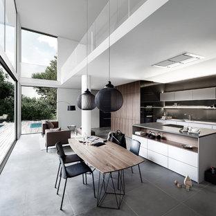 Bild på ett stort funkis kök med matplats, med vita väggar och skiffergolv