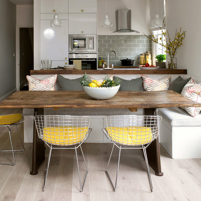 Trendy light wood floor and beige floor kitchen/dining room combo photo in London with white walls