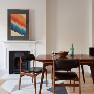 Inspiration for a medium sized scandi dining room in London with white walls, light hardwood flooring, a wood burning stove and a plastered fireplace surround.
